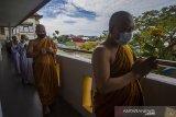 Bhikkhu Saddhaviro Mahathera (kanan) diikuti umat Buddha melakukan prosesi Pradaksina di Vihara Dhammasoka, Banjarmasin, Kalimantan Selatan, Rabu (26/5/2021). Pelaksanaan rangkaian hingga puncak upacara Tri Suci Waisak 2021 di vihara tersebut disiarkan secara online dan terbatas dengan menerapkan protokol kesehatan secara ketat untuk mencegah penyebaran COVID-19. Foto Antaranews Kalsel/Bayu Pratama S.