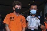 Kepala Badan Narkotika Nasional (BNN) Provinsi Bali Brigjen Pol Gde Sugianyar Dwi Putra (kanan) menunjukkan barang bukti dan tersangka kasus narkotika yang merupakan warga negara Rusia berinisial AG (kiri) saat konferensi pers di Kantor Badan Narkotika Nasional (BNN) Provinsi Bali, Denpasar, Bali, Jumat (28/5/2021). Petugas BNNP Bali dan Bea Cukai mengungkap kasus pengiriman narkotika jenis Dimethyltryptamine (DMT) seberat 194,42 gram yang dipesan tersangka AG dari Ukraina. ANTARA FOTO/Fikri Yusuf/nym.