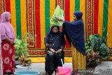 Tokoh adat (kanan) memandikan seorang warga yang usia kehamilannya memasuki usia tujuh bulan di Gampong Ilie, Banda Aceh, Aceh, Jumat (28/5/2021). Mandi tujuh bulanan dikalangan masyarakat Aceh merupakan tradisi dan adat warisan leluhur sebagai kesiapan seorang remaja yang telah menikah untuk menjadi seorang ibu serta membersihkan tubuh dengan berbagai rempah dan kembang. Antara Aceh/Irwansyah Putra.