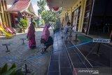 Anggota Kelompok Penyelenggara Pemungutan Suara (KPPS) berjalan memasuki ruangan untuk menjalani pemeriksaan tes cepat antigen di Kantor Kecamatan Banjarmasin Selatan, Banjarmasin, Kalimantan Selatan, Rabu (2/6/2021). Pada H-7 pelaksanaan Pemungutan Suara Ulang (PSU) pada 9 Juni 2021, KPU dan Bawaslu melakukan tes COVID-19 kepada 3.106 petugas di wilayah Banjarmasin Selatan yang akan bertugas saat PSU nanti. Foto Antaranews Kalsel/Bayu Pratama S.