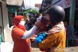 Relawan SIBAT PMI melakukan pengukuran suhu kepada salah seorang warga di Cisarua, Bogor. (Antara/HO/PMI/IFRC).