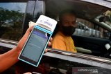 Seorang juru parkir menunjukan alat khusus digital untuk menghitung tarif parkir di daerah Urimessing Kota Ambon, Provinsi Maluku, Jumat (4/6/2021). ANTARA FOTO/FB ANGGORO)