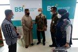 Wakil Direktur Utama 1 Bank Syariah Indonesia (BSI) Ngatari (tengah) didampingi CEO Regional BSI Aceh Nana Hendriana (kanan), Head Corporate Secretary and Communication Group BSI Rosalina Dewi (dua kanan) dan Deputi Bisnis Pembiayaan Regional Aceh BSI Saiful Musadir (kiri) berbincang dengan nasabah yang melakukan migrasi rekening di kantor area BSI Banda Aceh, Aceh, Senin (7/6/2021). BSI membuka 160 kantor cabang di 23 kabupaten dan kota untuk melayani 1,1 juta nasabah melakukan migrasi rekening  dan integrasi sistem operasional layanan di seluruh wilayah Aceh. Antara Aceh/Irwansyah Putra.