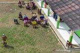 Foto udara sejumlah pasien terkonfirmasi positif COVID-19 berjemur saat menjalani isolasi mandiri di Madrasah Birrul Walidain, Rengasdengklok, Karawang, Jawa Barat, Selasa (8/6/2021). Sebanyak 28 orang terkonfirmasi positif COVID-19 yang berasal dari klaster mudik dan klaster wisata dirawat di ruang isolasi mandiri swadaya masyarakat guna mengantisipasi penularan COVID-19. ANTARA JABAR/M Ibnu Chazar/agr