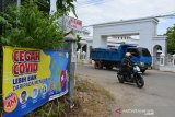 PENINGKATAN PROKES ZONA MERAH COVID-19. Pengendara sepeda motor mengenakan masker milintas di depan spanduk bertulis ajakan pencegahan COVID-19  di Posko Pemberlakuan Pembatasan Kegiatan Masyarakat (PPKM) Mikro kawasan zona merah COVID-19,  Desa Cot Masjid, Kecamatan Lhong Bata, Banda Aceh, Aceh, Rabu (9/6/2021). Satgas COVID-19  provinsi Aceh mengintruksikan kepada para camat dan kepala desa dalam wilayah Kota Banda Aceh sebagai peta zona merah (resiko tinggi) COVID-19 meningkatkan protokol kesehatan serta pemantauan terhadap sejumlah warga yang terpapar COVID-19 saat melakukan isolasi mandiri di rumahnya masing-masing. ANTARA FOTO/Ampelsa.