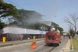 Petugas Dinas Pemadam Kebakaran Kota Surabaya menyemprotkan larutan disinfektan di area pos penyekatan Jembatan Suramadu, Surabaya, Jawa timur, Kamis (10/6/2021). Penyemprotan disinfektan dilakukan di area pos penyekatan yang menjadi tempat dilakukannya tes cepat antigen dan tes usap PCR bagi warga dari Pulau Madura yang menuju maupun melintas ke Surabaya, menyusul meningkatnya kasus COVID-19 di Bangkalan, Madura. Antara Jatim/Didik Suhartono/zk