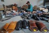 Pekerja menyelesaikan pembuatan sandal di Desa Samatan, Pamekasan, Jawa Timur, Kamis (10/6/2021). Sandal yang dipasarkan ke sejumlah daerah di Jatim dan Kalimantan dengan harga  antara Rp20 ribu hingga Rp150 ribu per pasang tergantung ukuran dan kualitas itu, produksinya terkendala minimnya  permodalan akibat Pandemi COVID-19. Antara Jatim/Saiful Bahri/zk