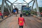 Petugas mengatur lalu lintas kendaraan yang melintasi Jembatan Sungai Kumpeh sebelum diperbaiki di Muara Kumpeh, Muarojambi, Jambi, Kamis (10/6/2021). Jembatan Sungai Kumpeh yang menghubungkan Kota Jambi dengan kawasan industri dan Pelabuhan Talang Duku di Kabupaten Muarojambi tersebut mendapatkan perbaikan bantalan karet dari Kementerian PUPR melalui Balai Pelaksanaan Jalan Nasional (BPJN) Wilayah Jambi. ANTARA FOTO/Wahdi Septiawan/foc.