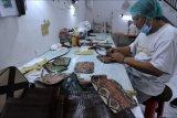 Pekerja UMKM menyelesaikan pembuatan produk kerajinan berbahan kulit di Badung, Bali, Jumat (11/6/2021). Kerajinan tas, dompet dan sejumlah aksesoris lainnya yang terbuat dari kulit ular dan sapi tersebut dijual dengan harga Rp200 ribu hingga Rp1 juta tergantung model dan diekspor ke berbagai negara seperti Inggris, Amerika Serikat, Singapura, dan Australia. ANTARA FOTO/Fikri Yusuf/nym.