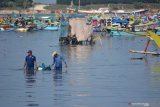 Nelayan membawa ikan hasil tangkapan menggunakan sterofoam atau keranjang di Pelabuhan Puger, Jember, Jawa Timur, Jumat (11/6/2021). Nelayan Puger beharapk Pemerintah Provinsi Jawa Timur selaku pengelola pelabuhan itu untuk menata pelabuhan seperti area sandar perahu agar tidak terlalu jauh sehingga nelayan dan pengangkut ikan tidak menyeberangi muara untuk membawa ikan ke Tempat Pelelangan Ikan. Antara Jatim/Seno/zk