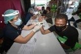 Petugas kesehatan melakukan skrining kepada pengemudi ojek online (ojol) saat vaksinasi COVID-19 di Denpasar, Bali, Sabtu (12/6/2021). Pemerintah Kota Denpasar gencar menggelar pelaksanaan vaksinasi COVID-19 untuk mengejar persentase vaksinasi di Kota Denpasar agar mencapai herd immunity atau 70 persen yang ditargerkan pada bulan Juli - Agustus 2021. ANTARA FOTO/Nyoman Hendra Wibowo/nym.