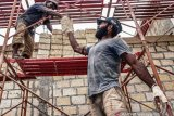 Warga asli Papua mengerjakan pembangunan venue layar PON XX