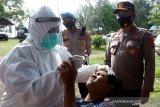 Petugas medis melakukan swab antigen pada warga yang terjaring razia protokol kesehatan (prokes) oleh tim satgas penanganan COVID-19 Kabupaten Aceh Besar di jalan nasional Banda Aceh - Meulaboh, Lhoknga, Aceh Besar, Aceh, Minggu (13/6/2021). Warga yang terjaring razia prokes dilakukan swab antigen dan diberi kesempatan untuk mendapat vaksin sinovac sebagai upaya pencegahan penularan COVID-19 dan percepatan penanganan pandemi yang kasusnya terus mengalami peningkatan di daerah itu. Antara Aceh/Irwansyah Putra.