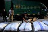 Petugas mengerahkan anjing pelacak untuk mencari paket narkotika jenis ganja yang disembunyikan di dalam karung pakaian bekas dan diangkut truk ekspedisi di Terminal Mengwi, Badung, Bali, Senin (14/6/2021) dini hari. Tim gabungan Direktorat Penindakan dan Pengejaran BNN RI dan Badan Narkotika Nasional (BNN) Provinsi Bali berhasil menggagalkan pengiriman 22 paket ganja seberat sekitar 44 kilogram dari Medan menuju Bali dan menangkap tersangka DPO bandar narkotika berinisial WG yang diduga merupakan pemilik barang bukti ganja tersebut. ANTARA FOTO/Fikri Yusuf/nym.