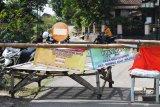 Pengendara melintas di dekat portal penutup akses menuju Desa Bantengan, Wungu, Kabupaten Madiun, Jawa Timur, Senin (14/6/2021). Penutupan jalan dilakukan setelah ditemukannya 66 warga Dusun Bulurejo, Bantengan dinyatakan positif COVID-19 setelah ada hajatan resepsi pernikahan hingga akhirnya akses keluar masuk wilayah tersebut ditutup guna pencegahan penularan COVID-19. Antara Jatim/Siswowidodo/zk