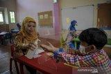 Seorang guru memberikan cairan pembersih tangan kepada seorang murid saat simulasi pembelajaran tatap muka (PTM) di Taman Kanak-kanak As-Salam, Bandung, Jawa Barat, Senin (14/6/2021). Pemerintah Kota Bandung mencatat dari 3.523 sekolah yang terdiri dari semua jenjang, hanya 319 sekolah yang dapat melaksanakan simulasi PTM setelah dinyatakan lolos verifikasi dari tim monitoring dan evaluasi gabungan. ANTARA JABAR/Raisan Al Farisi/agr
