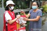 Relawan Palang Merah Indonesia (PMI) memberikan bantuan paket kesehatan kepada warga. (Antara/HO/PMI/IFRC).