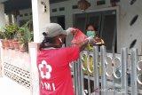 Relawan Palang Merah Indonesia (PMI) memberikan bantuan bahan pokok kepada keluarga yang sedang menjalani isolasi mandiri. (Antara/HO/PMI/IFRC).