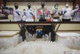 Polisi menunjukkan barang bukti saat ungkap kasus perdagangan benih lobster di Polda Jawa Timur, Surabaya, Jawa Timur, Selasa (15/6/2021). Ditreskrimsus Polda Jawa Timur menangkap WNT (33) dan RA (24) atas kasus dugaan memperdagangkan benih lobster serta mengamankan barang bukti diantaranya benih lobster jenis pasir sebanyak 30.000 ekor dan jenis mutiara sebanyak 500 ekor.  Antara Jatim/Didik Suhartono/zk