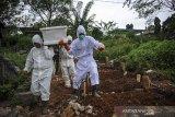Tenaga pikul membawa jenazah dengan protokol COVID-19 untuk dimakamkan di TPU Cikadut, Bandung, Jawa Barat, Selasa (15/6/2021). Petugas pikul jenazah mengatakan, pemakaman jenazah dengan protokol COVID-19 di TPU Cikadut mengalami peningkatan sebanyak 20 hingga 30 jenazah per hari dibandingkan dengan bulan lalu yang hanya lima hingga delapan jenazah per hari. ANTARA JABAR/Raisan Al Farisi/agr