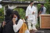 Keluarga menangis saat menyaksikan pemakaman jenazah dengan protokol COVID-19 di TPU Cikadut, Bandung, Jawa Barat, Selasa (15/6/2021). Petugas pikul jenazah mengatakan, pemakaman jenazah dengan protokol COVID-19 di TPU Cikadut mengalami peningkatan sebanyak 20 hingga 30 jenazah per hari dibandingkan dengan bulan lalu yang hanya lima hingga delapan jenazah per hari. ANTARA JABAR/Raisan Al Farisi/agr