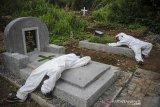 Sejumlah tenaga pikul beristirahat setelah memakamkan jenazah dengan protokol COVID-19 di TPU Cikadut, Bandung, Jawa Barat, Selasa (15/6/2021). Petugas pikul jenazah mengatakan, pemakaman jenazah dengan protokol COVID-19 di TPU Cikadut mengalami peningkatan sebanyak 20 hingga 30 jenazah per hari dibandingkan dengan bulan lalu yang hanya lima hingga delapan jenazah per hari. ANTARA JABAR/Raisan Al Farisi/agr