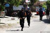 Personel Korps Brimob dari Mabes Polri melakukan pengamanan wilayah di Desa Bantengan, Wungu, Kabupaten Madiun, Jawa Timur, Selasa (15/6/2021). Mabes Polri menugaskan 25 personel Korps Brimob ke wilayah tersebut guna membantu pengamanan dan percepatan penanganan COVID-19 setelah adanya 88 warga dinyatakan positif COVID-19 dari klaster hajatan pernikahan, sehingga akses masuk maupun keluar wilayah dua RT ditutup. Antara Jatim/Siswowidodo/zk
