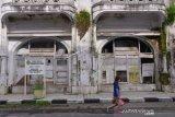 Warga melintas di depan bangunan bersejarah Gedung Warenhuis di Jalan Ahmad Yani VII, Medan, Sumatera Utara, Senin (14/6/2021). Pemerintah Kota Medan berencana akan merevitalisasi bangunan tersebut guna mengembangkan potensi wisata dan ekonomi. ANTARA FOTO/Fransisco Carolio/Lmo/foc.