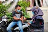 Relawan Palang Merah Indonesia (PMI) menyemprotkan hand sanitizer kepada warga. (Antara/HO/PMI/IFRC).