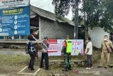 Relawan Palang Merah Indonesia (PMI) dibantu TNI/Polri memasang spanduk untuk mendukung upaya diseminasi informasi terkait COVID-19 kepada warga. (Antara/HO/PMI/IFRC).