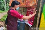 Relawan Palang Merah Indonesia (PMI) sedang memasang poster untuk melakukan diseminasi informasi terkait COVID-19 kepada warga. (Antara/HO/PMI/IFRC).