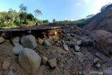 \Warga melinats do  jalan desa yang rusak akibat longsor di Desa Nglurup, Tulungagung, Jawa Timur, Jumat (18/4/2021). Longsor pada tebing sungai setempat  menyebabkan aliran sungai bergeser dan menggerus jalan beton menuju pemukiman di lereng Gunung Wilis itu, sehingga 270-an KK terisolasi. Antara Jatim/Destyan Sujarwoko/zk