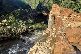 \ Warga melihat kondisi jembatan yang tertutup material longsor di Desa Nglurup, Tulungagung, Jawa Timur, Jumat (18/4/2021). Longsor pada tebing sungai setempat  menyebabkan aliran sungai bergeser dan menggerus jalan beton menuju pemukiman di lereng Gunung Wilis itu, sehingga 270-an KK terisolasi. Antara Jatim/Destyan Sujarwoko/zk