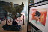 Seniman memainkan alat musik tradisional di antara lukisan yang dipamerkan saat pameran lukisan bertajuk Jejak Putera Sang Fajar di Perpustakaan Nasional Bung Karno Blitar, Jawa Timur, Jumat (18/6/2021). Pameran lukisan cat air yang memamerkan 30 lukisan karya 30 seniman lukis nasional asal Jogjakarta, Jakarta, Solo, dan Denpasar tersebut digelar dalam rangka jelang peringatan meninggalnya (Haul) Presiden Soekarno pada 21 Juni. Antara Jatim/Irfan Anshori/zk