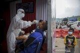 Petugas kesehatan melakukan tes usap antigen kepada pengendara saat operasi PPKM Mikro di Gerbang Keluar Tol Cileunyi, Kabupaten Bandung, Jawa Barat, Jumat (18/6/2021). Petugas gabungan memberikan layanan tes cepat antigen kepada pengendara dengan nomor polisi dari luar Kota Bandung yang akan menuju arah Sumedang, Garut, dan Tasik guna mencegah penyebaran COVID-19 di Jawa Barat yang sedang dinyatakan siaga satu COVID-19. ANTARA FOTO/Raisan Al Farisi/agr