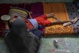 Warga Padaherang Samini menyuapi anaknya Iqbal Maulana yang menderita gizi buruk di Desa Peledah, Kecamatan Padaherang, Kabupaten Pangandaran Jawa Barat, Jumat (18/6/2021). Iqbal yang berusia 19 tahun dengan berat badan 12 kilogram tersebut menderita gizi buruk sejak berusia lima bulan. ANTARA FOTO/Adeng Bustomi/agr