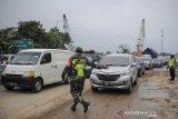Petugas TNI memberhentikan kendaraan dari luar Bandung untuk diperiksa saat operasi PPKM Mikro di Gerbang Keluar Tol Cileunyi, Kabupaten Bandung, Jawa Barat, Jumat (18/6/2021). Penyekatan kendaraan dari luar Bandung tersebut dilakukan setelah Jawa Barat dinyatakan siaga satu COVID-19 serta ditujukan untuk mencegah penyebaran COVID-19 di wilayah Bandung Raya. ANTARA FOTO/Raisan Al Farisi/agr