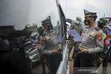 Petugas Kepolisian memeriksa surat keterangan sehat dari pengendara luar Bandung saat operasi PPKM Mikro di Gerbang Keluar Tol Cileunyi, Kabupaten Bandung, Jawa Barat, Jumat (18/6/2021). Penyekatan kendaraan dari luar Bandung tersebut dilakukan setelah Jawa Barat dinyatakan siaga satu COVID-19 serta ditujukan untuk mencegah penyebaran COVID-19 di wilayah Bandung Raya. ANTARA FOTO/Raisan Al Farisi/agr