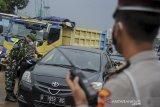 Petugas Kepolisian dan TNI memeriksa surat keterangan sehat dari pengendara luar Bandung saat operasi PPKM Mikro di Gerbang Keluar Tol Cileunyi, Kabupaten Bandung, Jawa Barat, Jumat (18/6/2021). Penyekatan kendaraan dari luar Bandung tersebut dilakukan setelah Jawa Barat dinyatakan siaga satu COVID-19 serta ditujukan untuk mencegah penyebaran COVID-19 di wilayah Bandung Raya. ANTARA FOTO/Raisan Al Farisi/agr