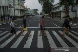 Sejumlah anak menyebrang di ruas jalan protokol kawasan Asia Afrika yang ditutup di Bandung, Jawa Barat, Jumat (18/6/2021). Warga terlihat menikmati suasana ruas jalan protokol di Kota Bandung yang lengang akibat ditutup untuk menekan peningkatan kasus aktif COVID-19 dan status siaga satu kawasan Bandung Raya. ANTARA FOTO/Novrian Arbi/agr
