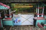 Seorang warga menengok kedalam kawasan wisata Air Terjun Cinulang yang ditutup di Cicalengka, Kabupaten Bandung, Jawa Barat, Sabtu (19/6/2021). Setelah Jawa Barat dinyatakan siaga satu COVID-19 oleh Gubernur Ridwan Kamil, pemerintah Kabupaten Bandung menutup semua destinasi wisata di Kabupaten Bandung hingga 21 Juni mendatang guna mencegah penyebaran COVID-19. ANTARA FOTO/Raisan Al Farisi/agr