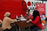 Petugas Palang Merah Indonesia (PMI) mememeriksa golongan darah calon pendonor sebelum dilakukan transfusi darah di dalam Mobil Unit Donor Darah di kawasan taman Sumber Wangi Kota Madiun, Jawa Timur, Sabtu (19/6/2021). Kegiatan bakti sosial yang digelar Partai Demokrasi Indonesia Perjuangan (PDIP) bekerja sama dengan PMI Kota Madiun tersebut dalam rangka peringatan Bulan Bung Karno 2021. Antara Jatim/Siswowidodo/zk