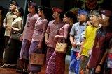 Model memperagakan busana kerja adat Bali saat Lomba Desain dan Peragaan Busana rangkaian Pesta Kesenian Bali ke-43 di Denpasar, Bali, Minggu (20/6/2021). Kegiatan yang melombakan kreasi desain busana kerja, kasual dan pesta dengan menggunakan bahan tekstil tradisional Bali tersebut diselenggarakan untuk melestarikan produk-produk tekstil tradisional khas Bali dan mendorong produksi pelaku UMKM lokal. ANTARA FOTO/Fikri Yusuf/nym.