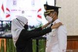 Gubernur  Jawa Timur Khofifah Indar Parawansa (kiri) menyematkan tanda pangkat dan tanda jabatan kepada Bupati Tuban Aditya Halindra Faridzki (kanan) saat Pengambilan Sumpah Jabatan dan Pelantikan Bupati dan Wakil Bupati Tuban Hasil Pilkada Serentak Tahun 2020 di Gedung Negara Grahadi, Surabaya, Jawa Timur, Minggu (20/6/2021). Pelantikan Bupati dan Wakil Bupati Tuban masa jabatan 2021-2024 tersebut digelar secara langsung untuk Bupati Tuban Aditya Halindra Faridzki, namun untuk Wakil Bupati Tuban Riyadi digelar secara virtual. Antara Jatim/Didik Suhartono/zk