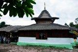 Sejumlah wisatawan lokal mengunjungi Masjid Wapauwe di Negeri (Desa) Kaitetu Kabupaten Maluku Tengah, Provinsi Maluku, Minggu (20/6/2021). Masjid Wapauwe merupakan masjid tertua di Maluku, dibangun pada 1414 di daerah Wamane dan menurut legenda warga setempat masjid itu berpindah sendiri ke lokasi sekarang pada 1664, dan kini menjadi objek wisata religi karena arsitektur uniknya yang dibangun tanpa paku dan nilai historisnya tentang penyebaran Islam di Maluku. (ANTARA FOTO/FB Anggoro)