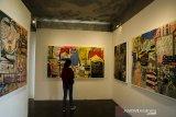 Pengunjung melihat karya seni lukis yang dipajang pada pameran Seni Rupa Tumpang Tindih di Orbital Dago, Bandung, Jawa Barat, Minggu (10/6/2021). Pameran karya Seniman Donni Arifianto tersebut menampilkan teks, jargon, citra periklanan hingga kartun dan ilustrasi yang terus muncul dan berekspresi dalam kehidupan dan media sosial. ANTARA FOTO/Novrian Arbi/agr