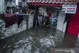 Warga membersihkan sampah yang terbawa arus banjir di kawasan Kacapiring, Bandung, Jawa Barat, Senin (21/6/2021). Puluhan rumah di kawasan tersebut terendam banjir setinggi 30 cm hingga dua meter akibat intensitas curah hujan yang tinggi dan luapan Sungai Cikudapateuh Dalam. ANTARA FOTO/Novrian Arbi/agr