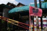 Petugas berjaga di posko Pemberlakukan Pembatasan Kegiatan Masyarakat (PPKM) Mikro yang ditandai bendera merah di Desa Sewulan, Dagangan, Kabupaten Madiun, Jawa Timur, Senin (21/6/2021). Pemasangan bendera merah berlogo Satuan Tugas Penangan COVID-19 tersebut dimaksudkan sebagai penanda bahwa kawasan tersebut berstatus zona merah COVID-19 dengan pengawasan ketat terhadap mobilitas warga guna pencegahan penyakit akibat virus corona. Antara Jatim/Siswowidodo/zk
