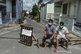 Warga berjaga di salah satu jalan akses menuju kawasan RW 04 Kampung Sambongpari, Kota Tasikmalaya, Jawa Barat, Senin (21/6/2021). Warga RW 04 di Kampung Sambongpari tersebut melakukan karantina wilayah mandiri menyusul 15 warganya terkonfirmasi positif COVID-19, satu di antaranya meninggal dunia usai berwisata ke Pangandaran. ANTARA FOTO/Adeng Bustomi/agr