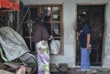 Dua orang warga memberikan bantuan sembako kepada kerabatnya yang sedang menjalani isolasi mandiri di Kampung Sambongpari, Kota Tasikmalaya, Jawa Barat, Senin (21/6/2021). Warga RW 04 di Kampung Sambongpari tersebut melakukan karantina wilayah mandiri menyusul 15 warganya terkonfirmasi positif COVID-19, satu di antaranya meninggal dunia usai berwisata ke Pangandaran. ANTARA FOTO/Adeng Bustomi/agr